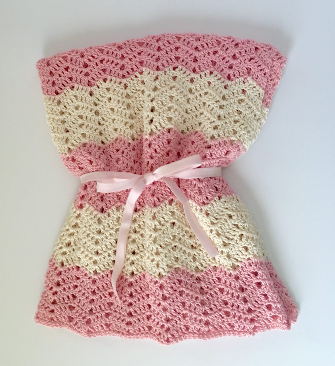 Peek a Boo Baby Blanket crochet pattern by little monkeys designs in cream and pink