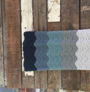 A wedding afghan crochet pattern to crochet a blanket in the couple's wedding colors. Crochet blanket pattern in a fun ripple stitch by Little Monkeys Design.